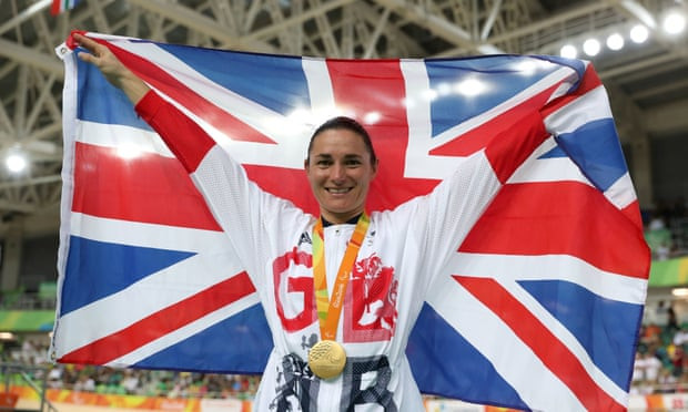 Cycling gold medallist Dame Sarah Storey on the top step of the podium in Rio. She will be competing in her eight Paralympics in Tokyo. She is a white woman with briwn hair tied into a bun. She wears a gold medal around her neck and holds a United Kingdom flag high behind her. She smiles at the camera broadly