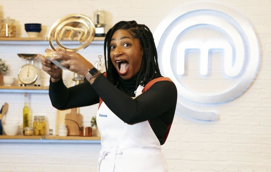 A beautiful young black woman smiles jokingly with her mouth open and looks at the camera while holding a large gold Masterchef Trophy. She has long braided hair to her shoulders and wears a black polo neck with a white apron. Behind her is a Masterchef logo on the wall which is a white letter m surrounded by a white spiral.
