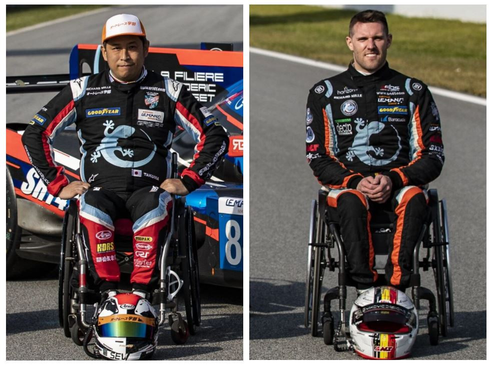 Two men sit in wheelchairs wearing racing overalls and have racing helmets at their feet.