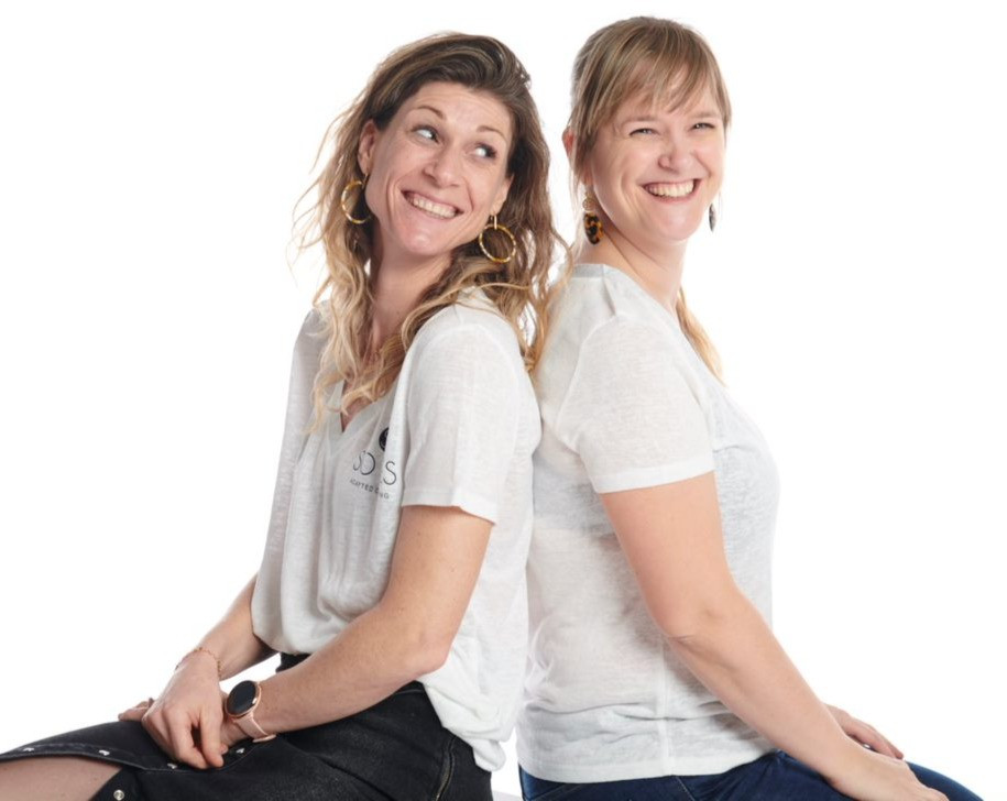 Jessie and Sofie sit back to back and smile facing the camera. They are both white with long hair, Jessie wears hers long and Sofie has her hair tied in a ponytail and has a fringe. They both wear white tee shirts and black jeans