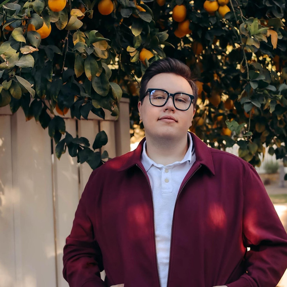 A white person stands facing the camera, hey have short dark hair brushed back into a quiff, they wear navy blue rimmed glasses, a burgundy zipped jacket with a white two buttoned polo shirt underneath. They stand with their hands in their pockets and behind them is a wooden fence with an orange tree heavy with fruit above it.