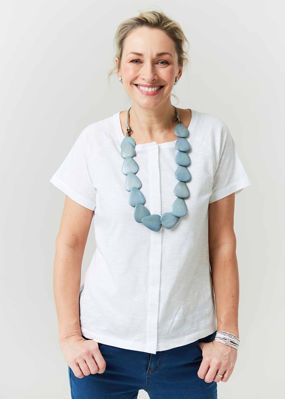 A blonde lady is smiling at the camera, her hair tied up in a messy bun. She wears a white tee shirt, with a front velcro closure a large statement blue necklace and blue jeans. Her thumbs are in her pockets.