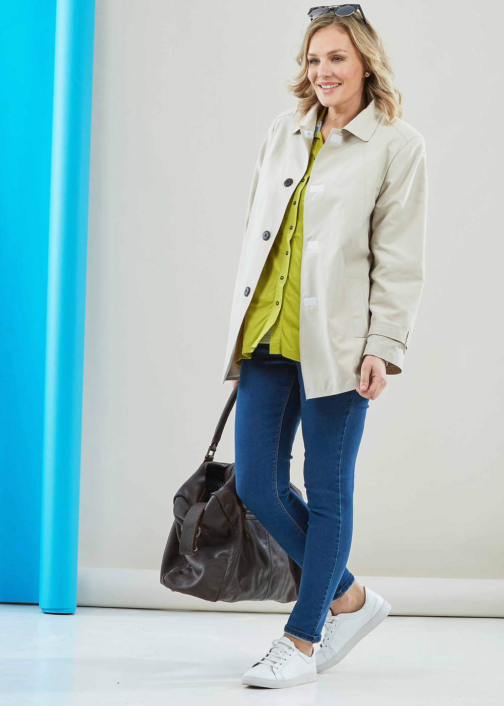 A blonde woman stands with a hip length cream coloures, a lime green shirt underneath, denim jeans and white trainers. She has a bag in her right hand and sunglasses on top of her head