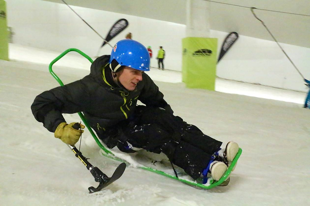 A para skier zooms down the snow slope on a green sit-ski. They are wearing a black padded snow suit and blue helmet.