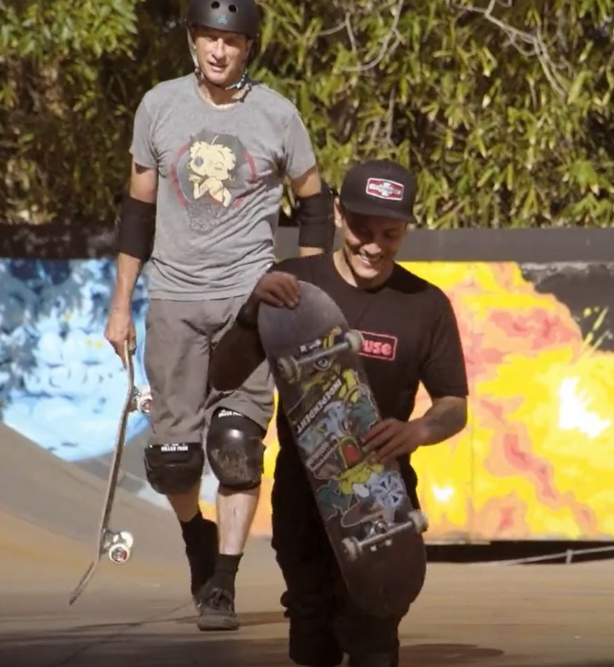 Two men walk towards the camera holding skateboards. Tony Hawk, a white man wearing a skateboarding helmet, knee and elbow pads wears a grey tee shirt with betty boop print on the front with grey knee length shorts. Felipe Nunes is a latino man with two amputated limbs just above the knee. He is not wearing prosthetics. He wears a black baseball cap and black tee shirt and shorts. They are walking in a skatepark with a colourful ramp in the background.