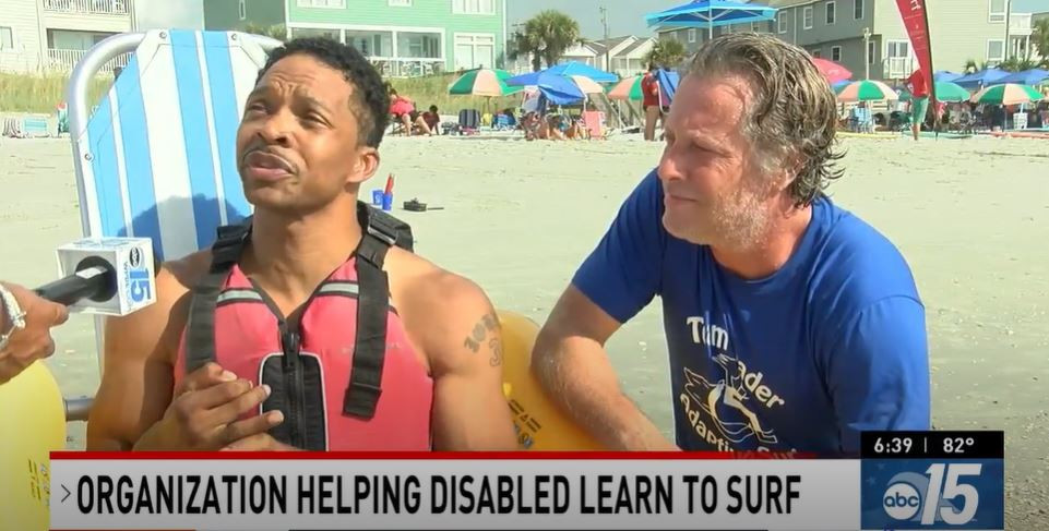 Two men sit on the beach being interviewed by a reporter. On the left is a middle aged black man with short black hair. He wears a water buoyancy vest. On the right is a middle aged white man, he has tousled grey and brown hair and wears a blue tee shirt. A banner at the bottom of the image reads 'Organization helping disabled learn to surf' ABC 15.