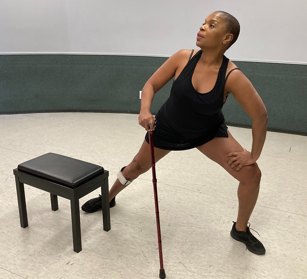 Zazel lunges to the left, she is in an empty space apart from a small stool in front of her. She holds a walking stick in her right hand and has a brace visible on her right leg. She wears a sleeveless black top, black shorts and black shoes.