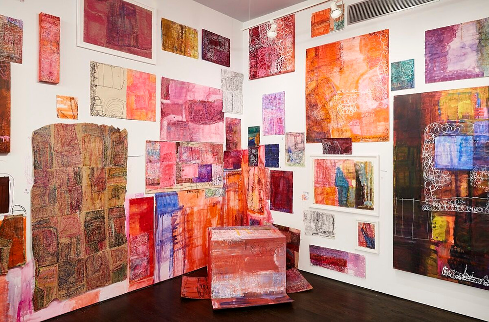 A roomful of colourful prints are visible in an art exhibiltion. The wall is white and the floor is black, the prints are in shades of pink, orange and red with hints of blue.