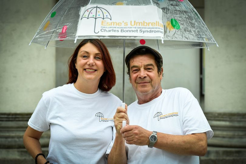 """A white slim middle aged woman with a brown bobbed haircut stands on the left and a slim middle aged man with short dark hair and black flat cap stands on the right. The both smile at the camera and wear matching white tee shirts. They hold a clear plastic umbrella above them that reads the charity name """"Esme's Umbrella"""""""