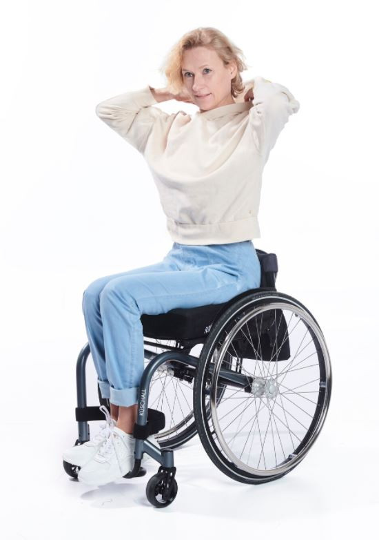 A white woman with short blonde hair sits in her wheelchair, she is wearing light blue denim jeans and a cream long sleeve sweatshirt with white trainers