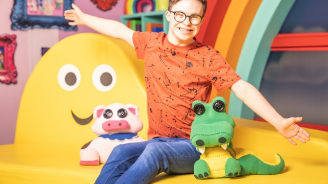 A young white man with downs syndrome sits in a brightly coloured tv set. He sits on a bright yellow bench with a smiley face on it. He has a toy pig and a toy crocodile beside him. His arms are outstretched and he wears a bright orange t-short and blue jeans.
