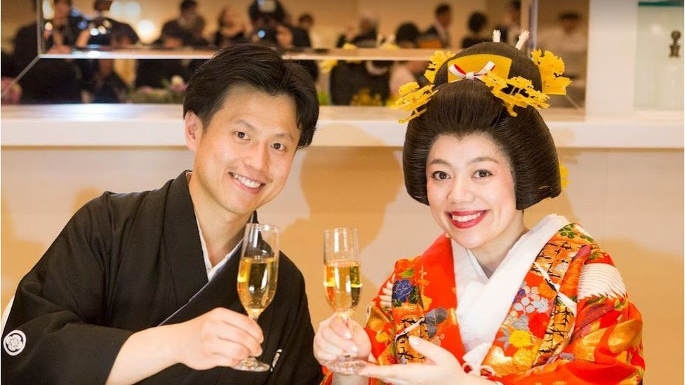 A japanese couple smile at the camera while holding glasses of champagne. The man on the left has dark hair and wears traditional black wrapped clothing. The woman on the right wears a red floral kimono with pale make up and red lips. She has black hair tied up with a golden ornate hair clip.