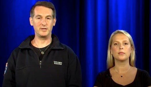 Avi is standing beside a blonde lady and they both wear black. There is a blue curtain behind. They are speaking to a camera.
