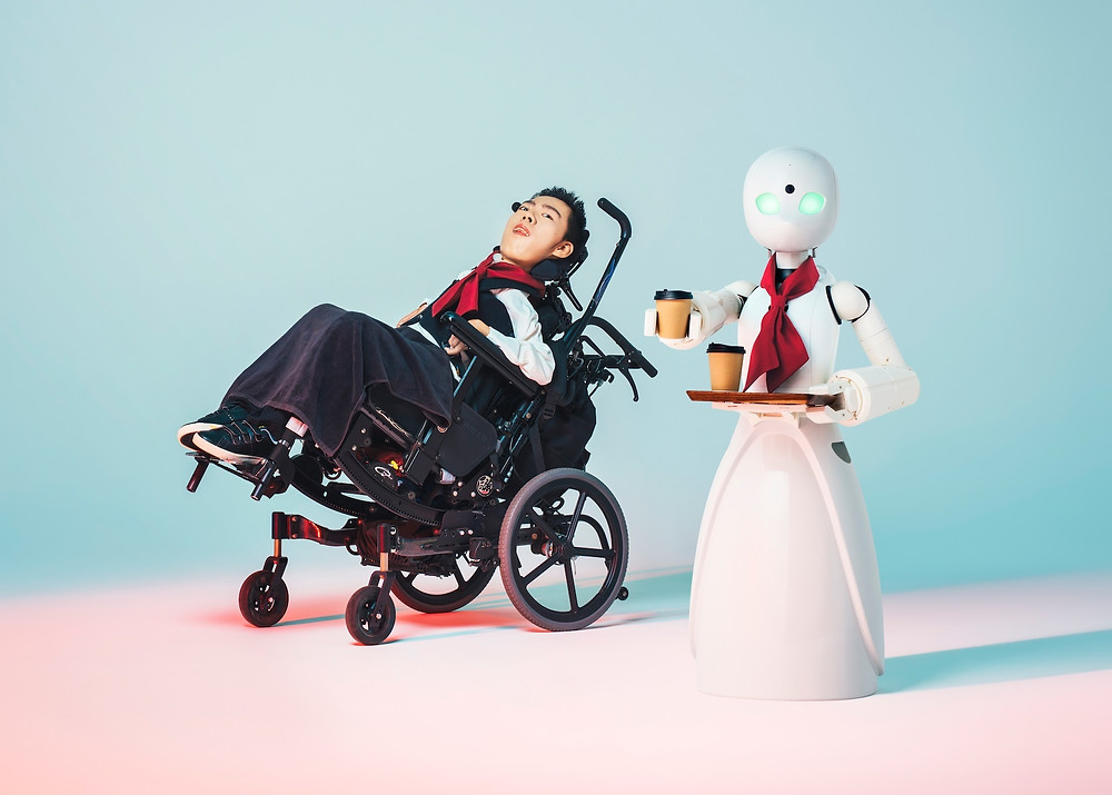 A japanese man sits in a wheelchair. He has black short hair and wears black and red long sleeve top, black wide legged jeans and black trainers with white soles. Beside him is a white robot with green lighted eyes. the robot looks at the camera wearing a red neck scarf and carries a tray with two take-away beverages. The robot holds one beverage in its hand.