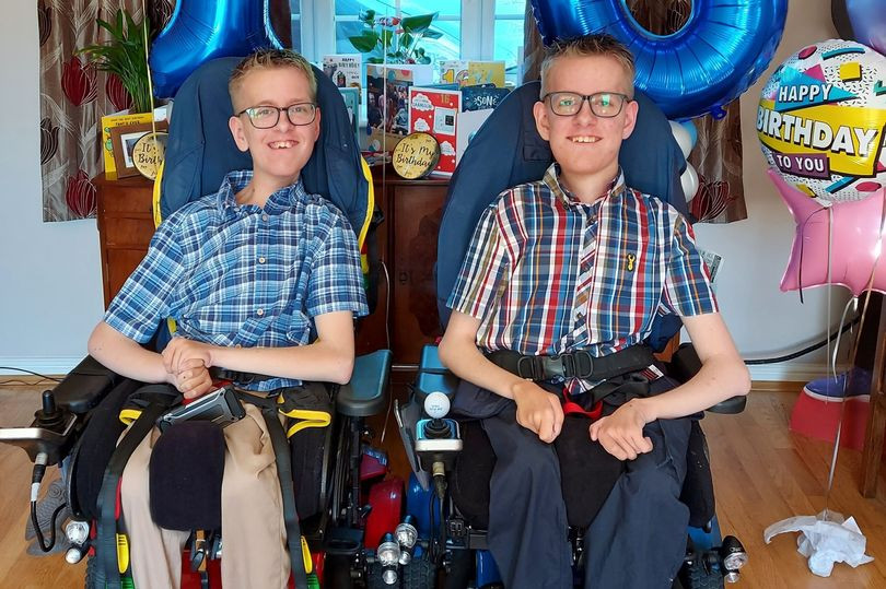 Two young men are sat in blue and black wheelchairs smiling at the camera. They are both blonde and wear dark rimmed glasses, check short sleeve shirts and trousers. One wears blue trousers and the other wears cream trousers. There are birthday balloons floating beside them.