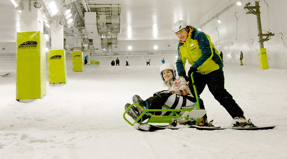 A para skier and her instructor are zooming down the slope, he pushes her sit ski from behind