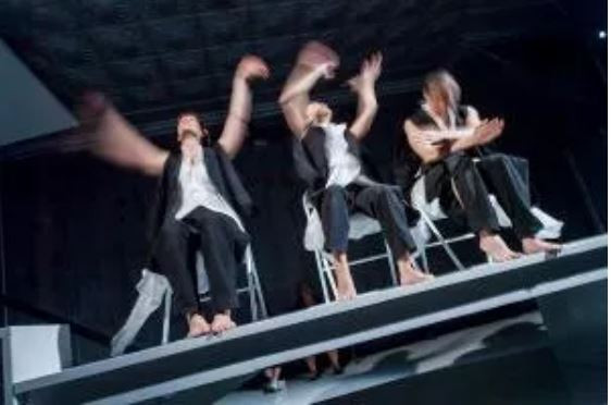 An image of three performers on a stage, the image is blurred indicating their movement. They all wear black trousers, white shirts and black waistcoats which are open. They are all barefoot.