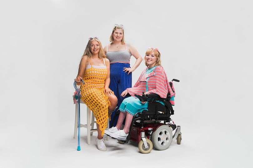 Three blonde white women are sitting and smiling while facing the camera in a white studio background. The girl on the left wears a knitted yellow full length dress, white vest underneath and white trainers. She is seated on a stool holding a blue cane. The girl standing in the centre wears a white crop top and blue high waisted trousers. The girl to the rights sits in a mauve and black wheelchair. She wears a turquoise dress and a pink cape.