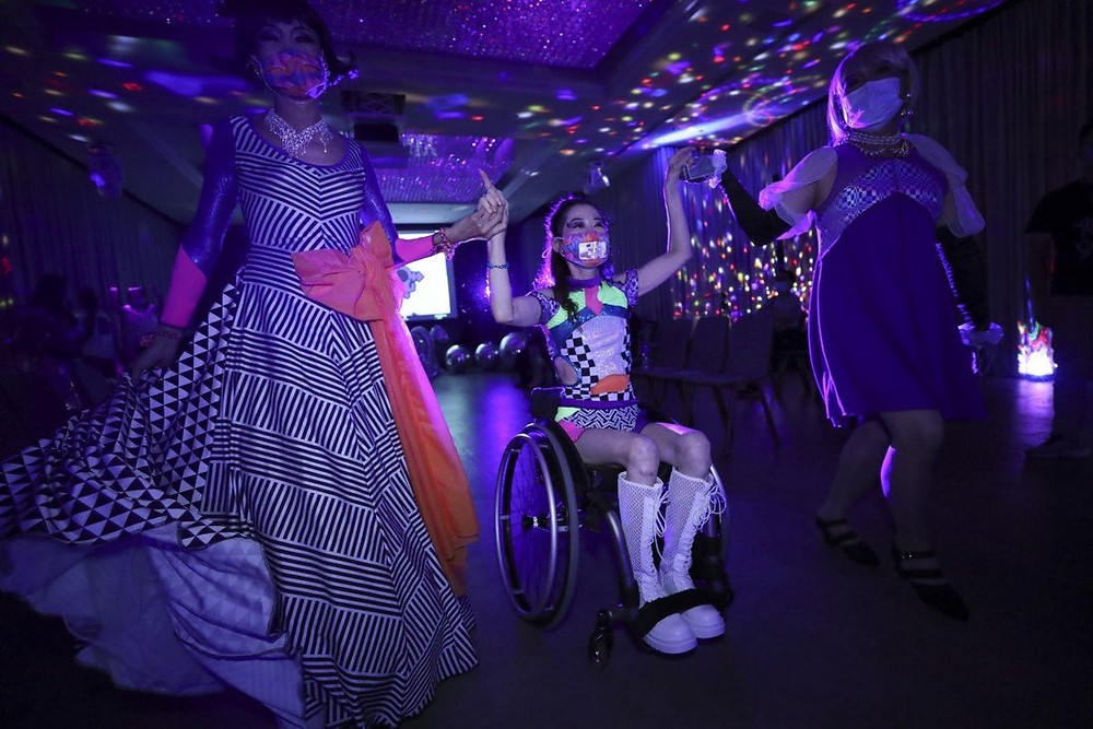 Three Chinese models are on a runway in neon lighting. The lady standing on the left wears a long black and white striped full skirted dress with a large pink bow on the waist. The lady in the centre is in a wheelchair and wears a black and white checked body suit with neon yellow panels on the stomach and shoulders with knee high front laced white boots. The lady standing on the right wears a blue knee lengths dress with a silver throw and black pumps. All models are wearing masks.