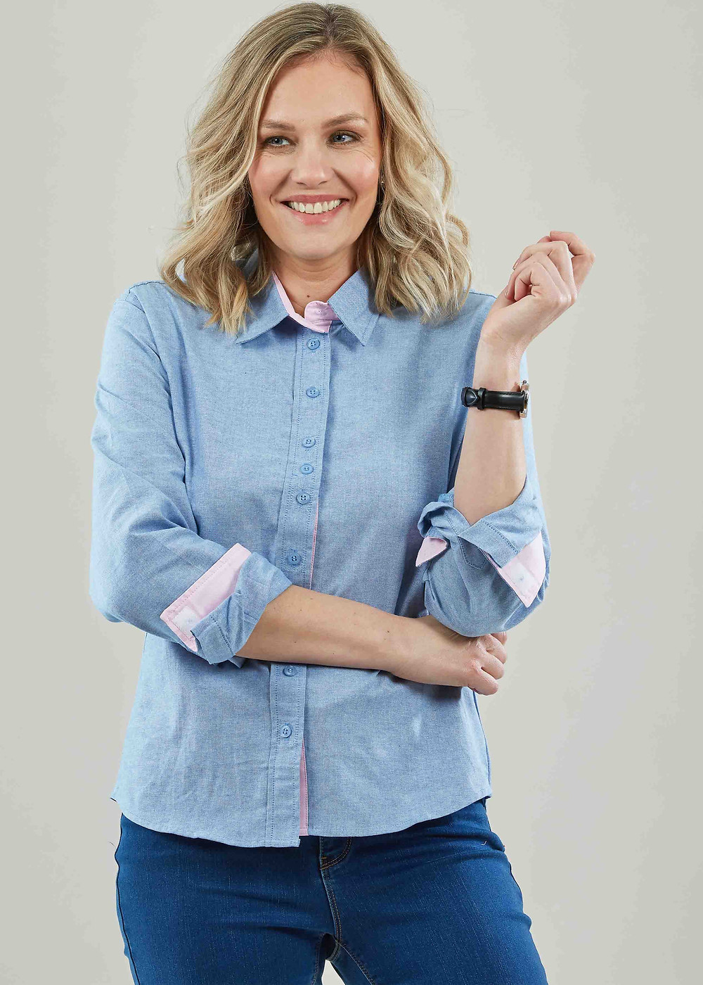 A blonde woman wears a blue long sleeved s with pink cuffs and collar trim. It has fake button detail on the centre front and cuffs and closes using velcro. She wears dark blue jeans.