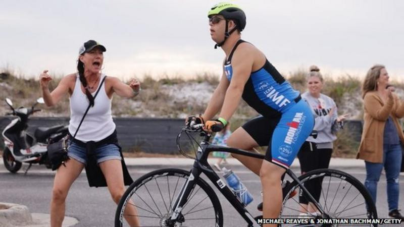 A man with downs syndrome is on a road racing bicycle. He wears a green and black cycling helmet with a blue and black lycra triathlon suit with some sponsored logos printed on it. He is looking into the distance and in deep concentration. A spectator stands in the background excitedly cheering him on. She wears a white tank top, blue denim shorts and a baseball cap. Her arms are raised and she is shouting encouragement.