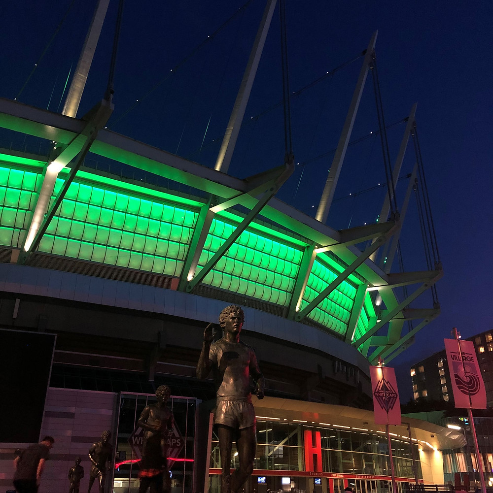 A stadium is visible with bright green lighting against the dark night sky. A bronze statue of a man is in front of the stadium.