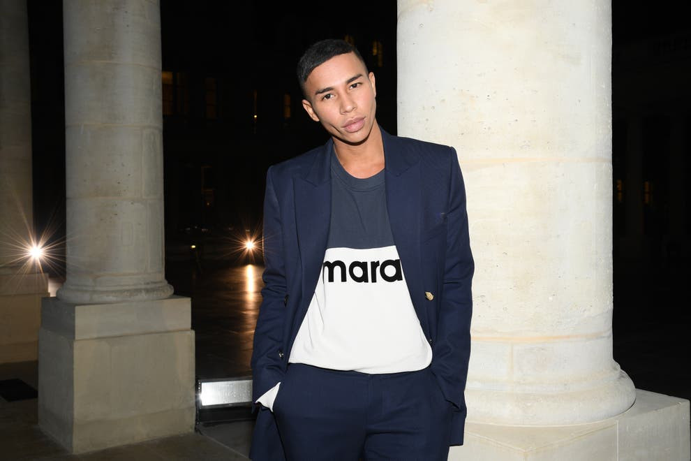Olivier is a young black man with short black hair, wearing a stylish navy suit with a navy and white top underneath. He poses for the camera with his hands in his pockets and stands in front of large pillars on a building.