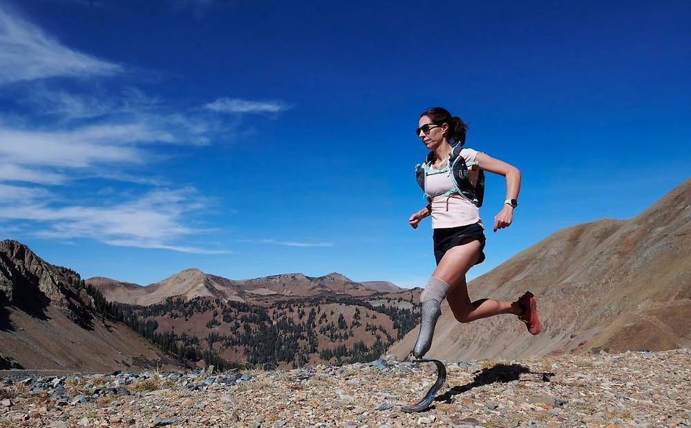 A white woman with brown hair in a ponytail is running through a mountain trail, a beautiful view of mountains and blue sky is visible behind her. She wears a judration backpack, white t-shirt and black shorts. On one leg she has a running blade to her knee with a grey socket sock.