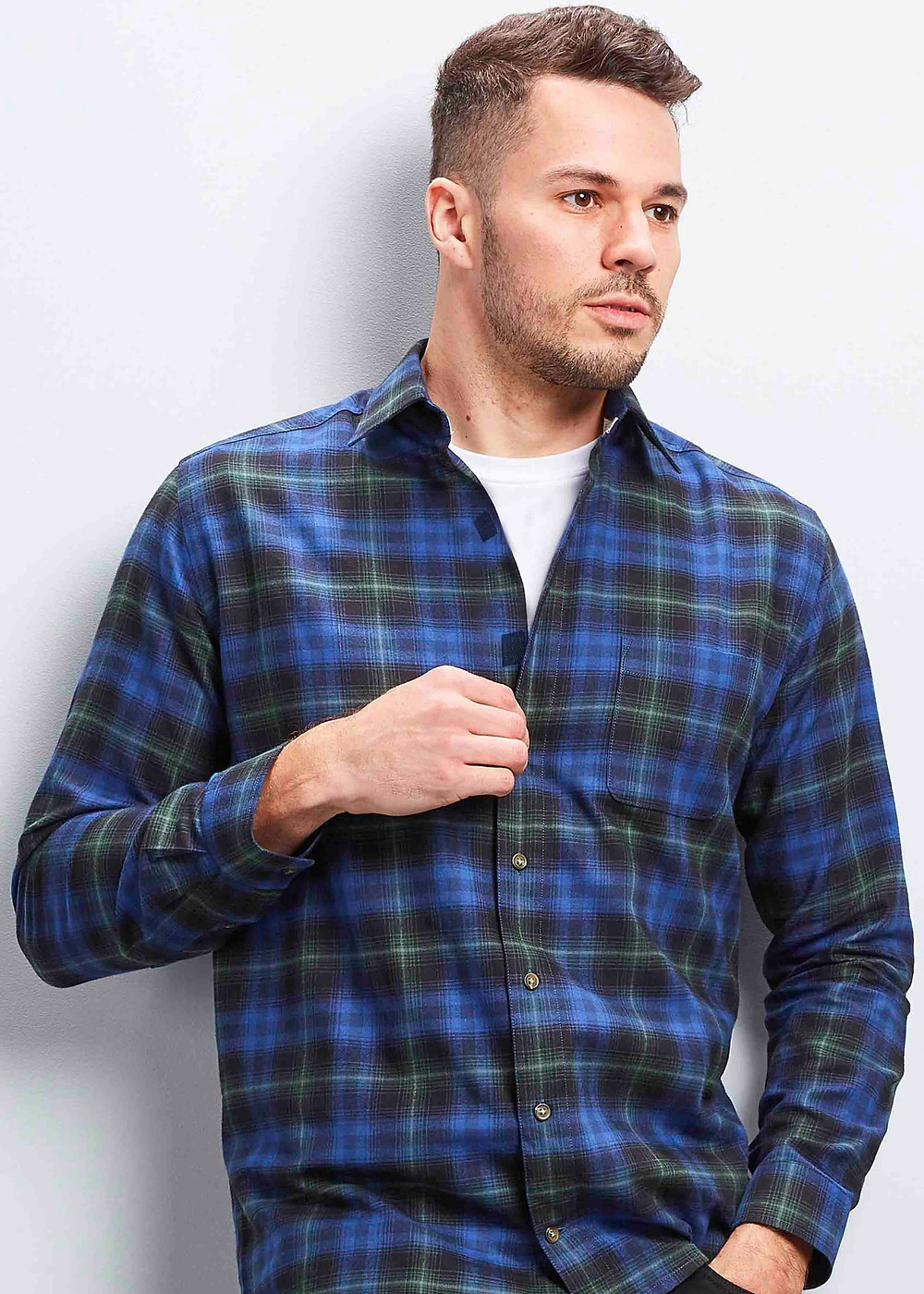 A white man with short brown hair wears a blue and green plaid checked short with long sleeves, fake buttons and velcro closures. he wears a white tee shirt underneath and black jeans. He has one hand in his pocket.