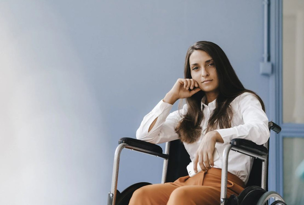 A white woman with long brown hair sits in a wheelchair. She rests her elbow on the armrest and her chin rests on her hand. She looks at the camera confidently and wears a white long sleeved button shirt with rust coloured trousers. She is in front of a pale blue wall.