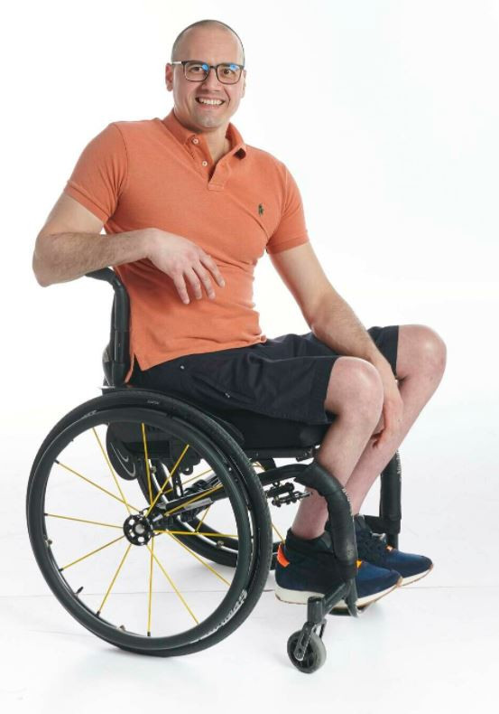 A white man who is bald and wearing glasses sits in his wheelchair. He is wearing an orange polo shirt with navy adaptive shorts and navy shoes
