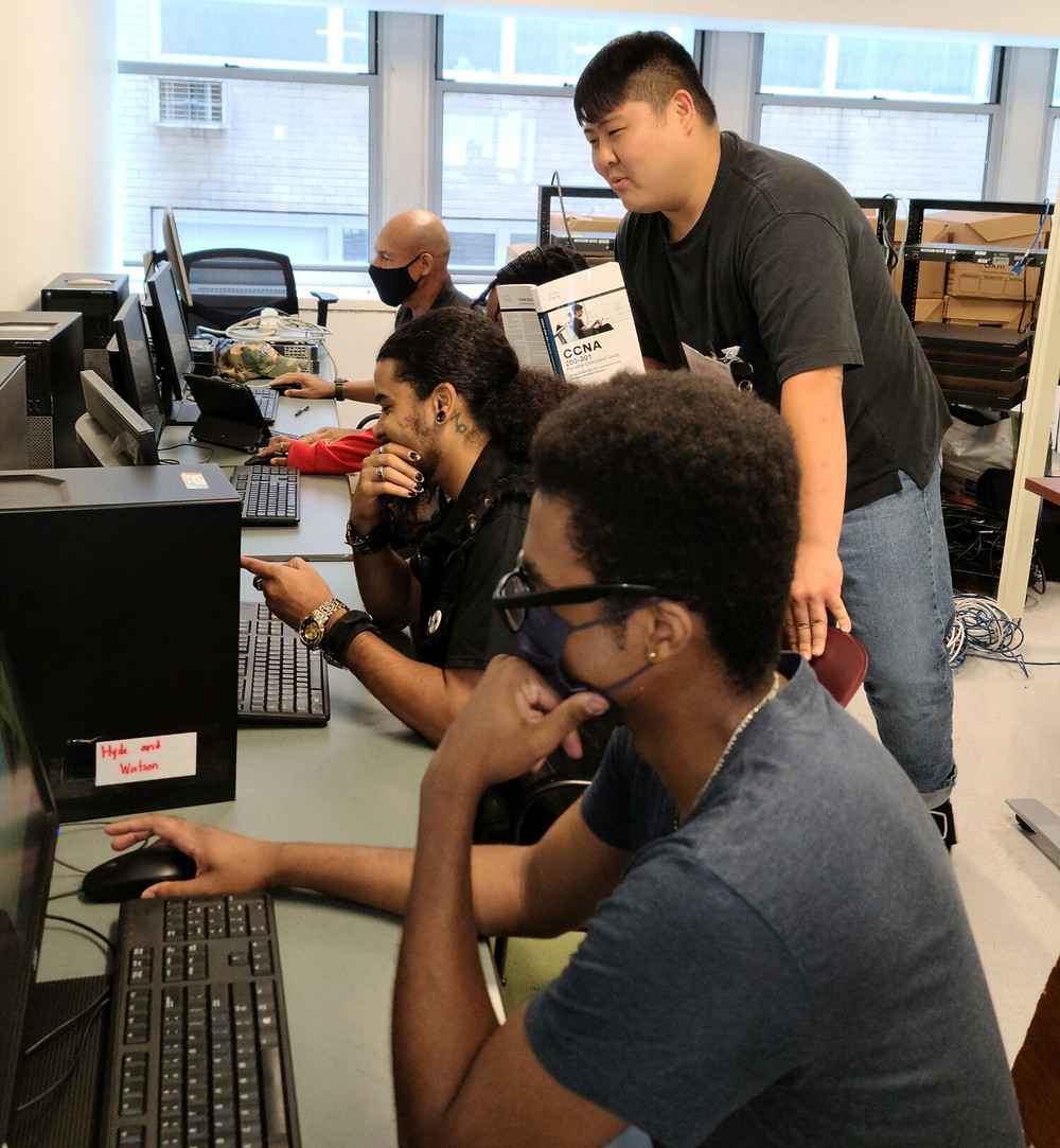 An Asian man stands over two men working at computer desks. He is teaching them.