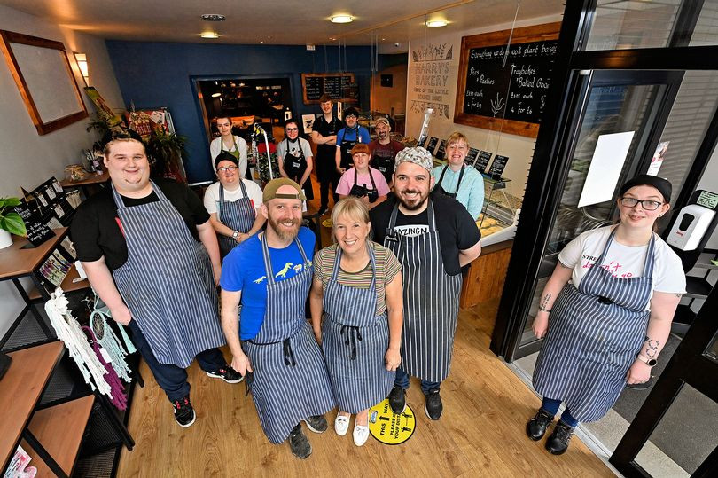 A group of cafe staff stand in their cafe looking up at the photographer. They all smile and are wearing matching striped blue and white aprons.