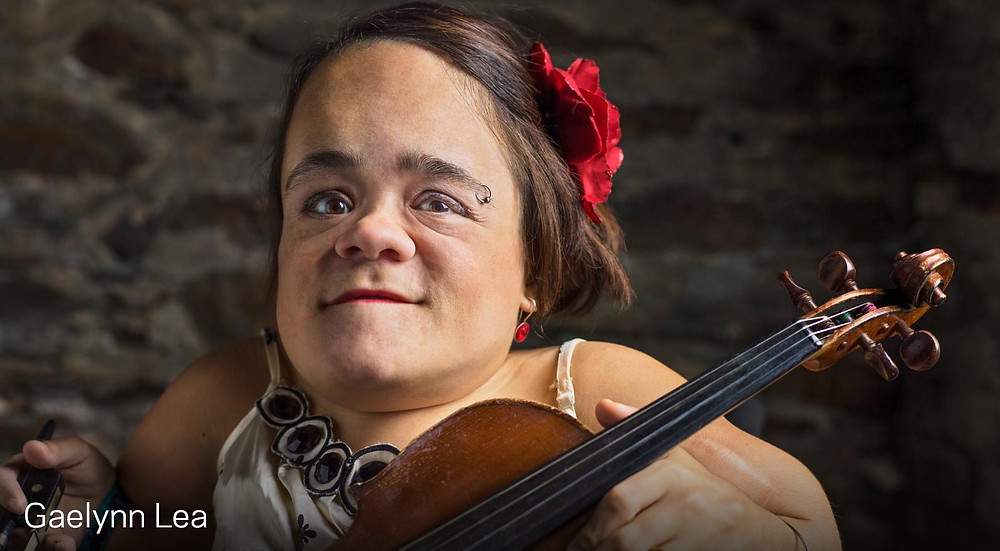 A young woman with dwarfism smiles at the camera, she has long chestnut hair tied into a bun and has a large red flower in a clip on the side of her hair. She holds a violin in front of her.