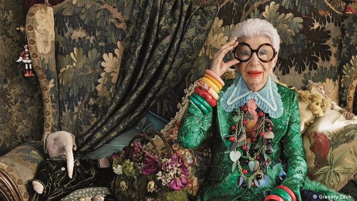 Iris Apfel is a Jewish white elderly lady with short styled white hair. She wears her statement large circular glasses with black rims and red lipstick. She holds one side of her glasses with her right hand, showing 6 large bangles of various colours, She wears an embroidered emerald green coat and a white large lace collar; She has several large necklaces made with beads, leaves and hearts. She sits in an opulent floral vintage chair with silk floral cushions. A toy vintage elephant teddy bear is also visible beside her.