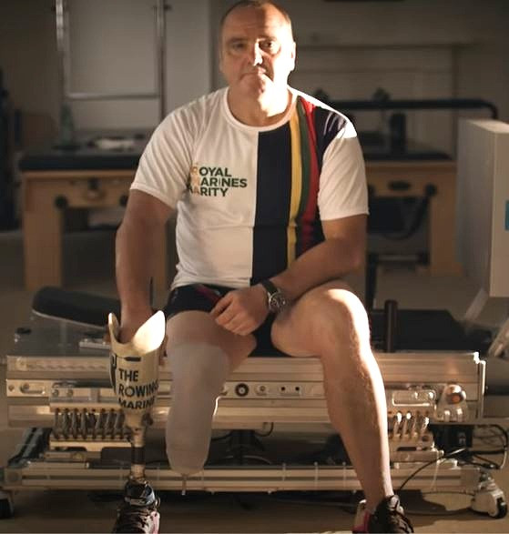 A white middle aged man sits on the edge of a bench, his right leg is amputated below the knee and he holds a prosthetic limb in his right hand. He weard a Royal Marines Charity tee shirt and black shorts with black running shoes. He looks straight at the camera.