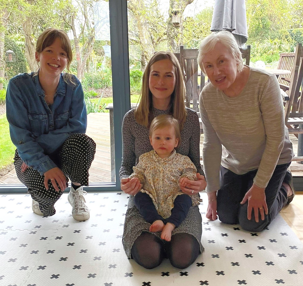 On the left is Felicity, she is kneeling wearing a blue denim shirt and grey trousers. She is a white woman with brown hair in a ponytail. Centre is Katie, she has long blonde hair and wears a grey dress. On her knee is Eva, a baby with blonde hair. On the right is Katies grandmother, she has grey short hair and wears a cream jumper with black trousers and s kneeling down.