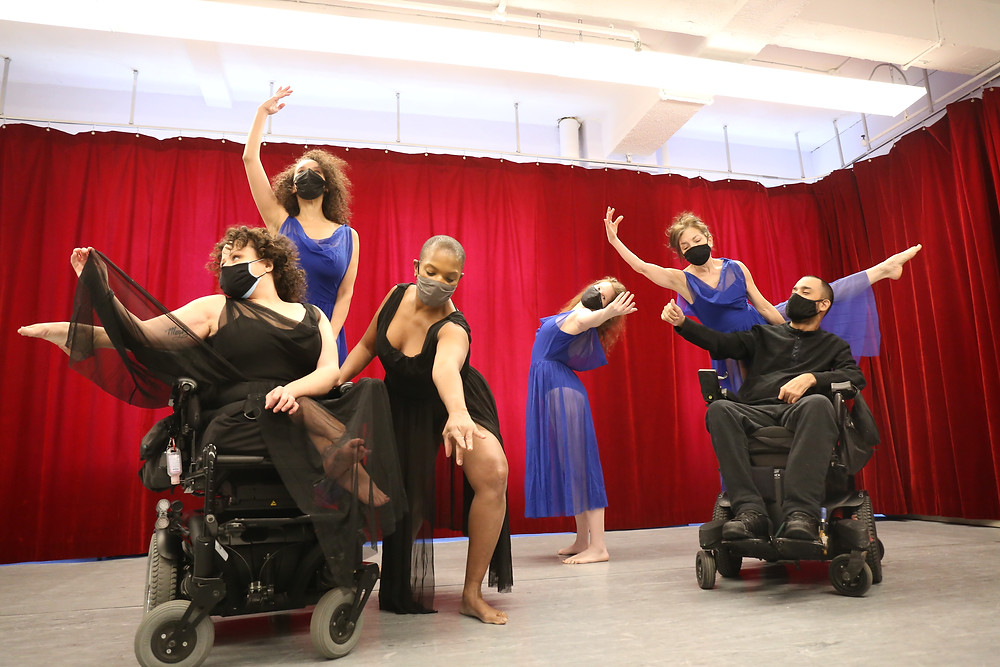 Six performers are dancing with red curtains behind them. Two dancers are seated in wheelchairs, both dressed in black. Zazel is centre of the image in a pose wearing black with a flowing chiffon skirt. Three other dancers all in poses are dressed in purple with flowing chiffon skirts.