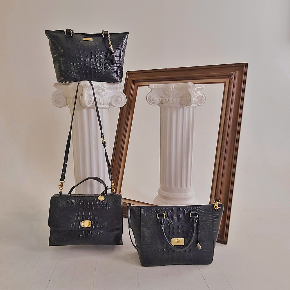 Three handbags arranged on and in front of pedestals and an empty picture frame