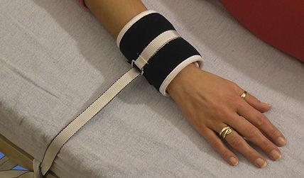 FIxierung der Hangelenke mittels gepolsterete Handgelenkfixationsgurte.