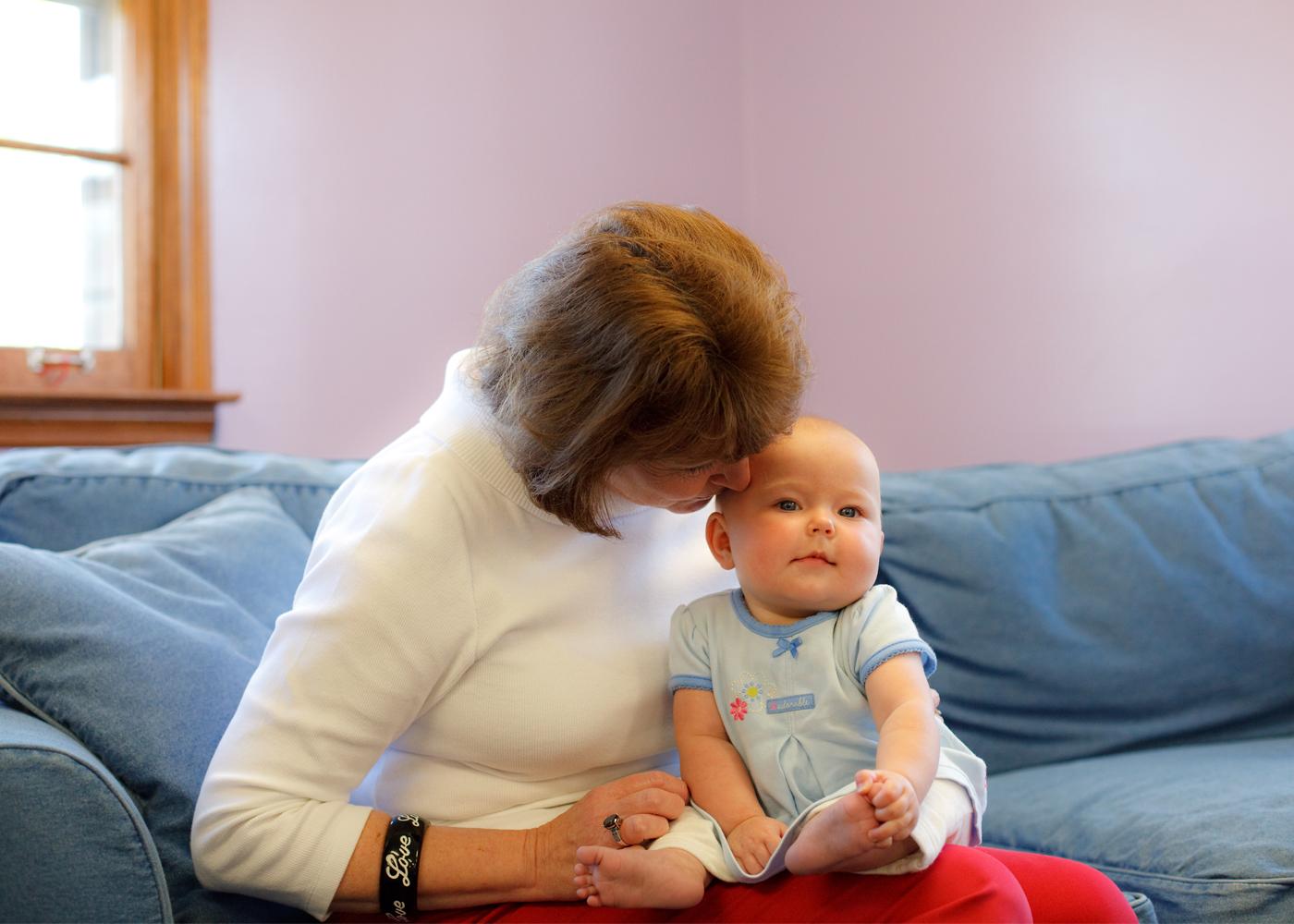 Women holding white baby
