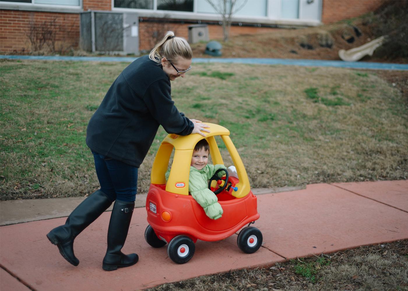 Women pushing kid in play car