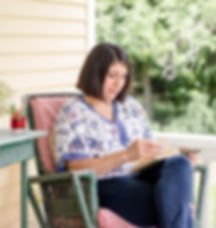 Bed and breakfast guest reading book on porch
