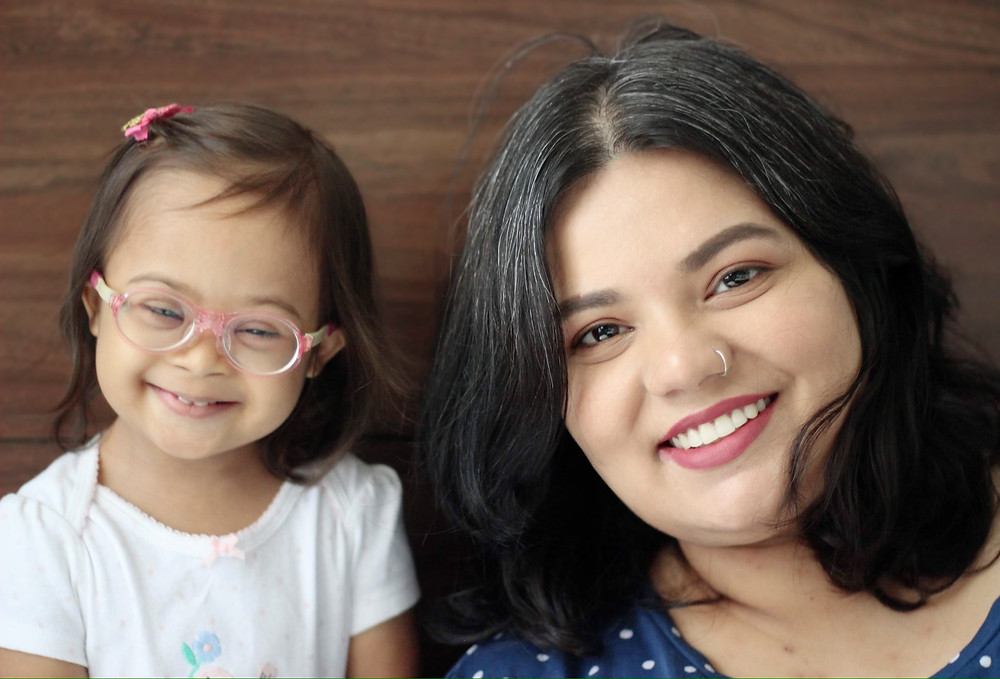 An Indian woman with her daughter who has Downs syndrome smiling for the camera