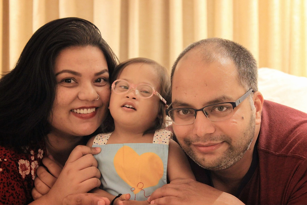 Indian Man and Woman smiling at their camera with their daughter who has Downs Syndrome