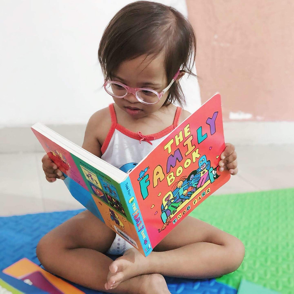 Indian Toddler with Down Syndrome reading a book