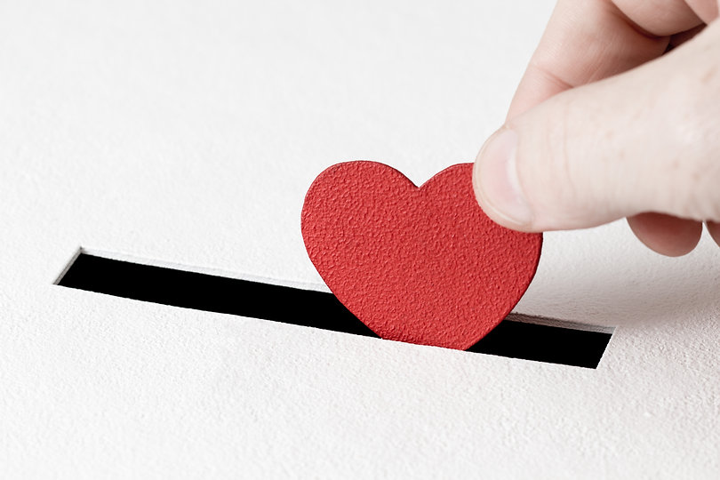 Red heart symbol is put by person's hand