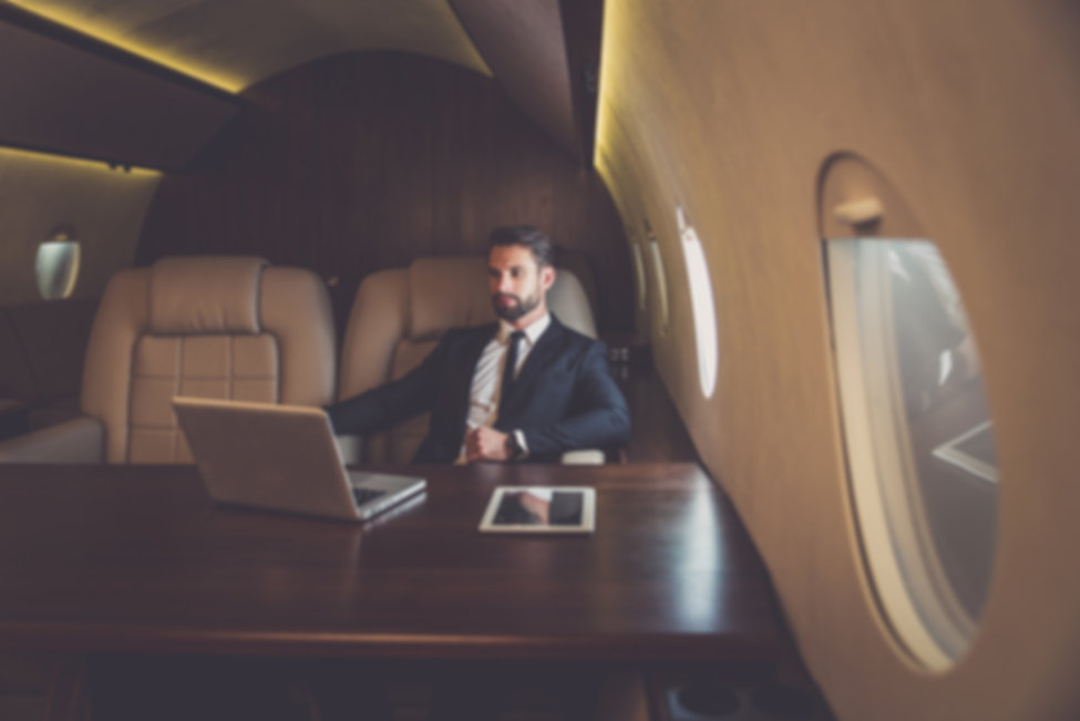 Business man flying on a private jet. Wo