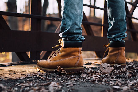 man wearing boots standing on bridge.jpg