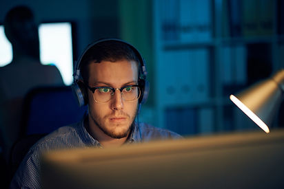young-programmer-in-eyewear-and-headphon